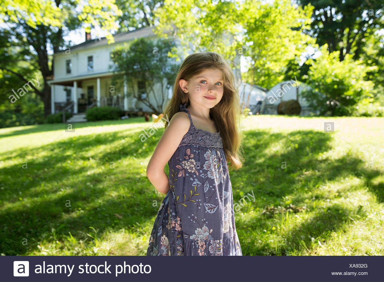 Outdoors in summer. On the farm. A girl in the garden with her hands behind her back. - Stock Image