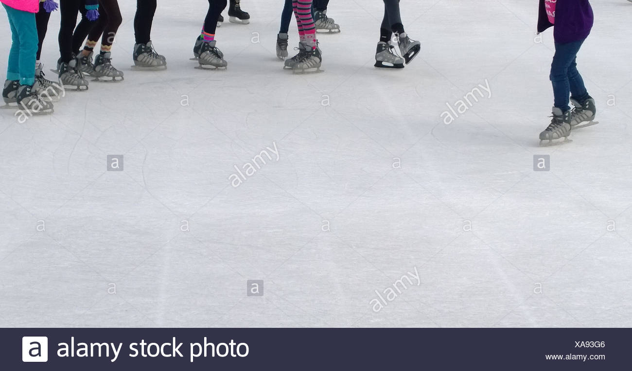 Close-up of people's legs ice-skating - Stock Image