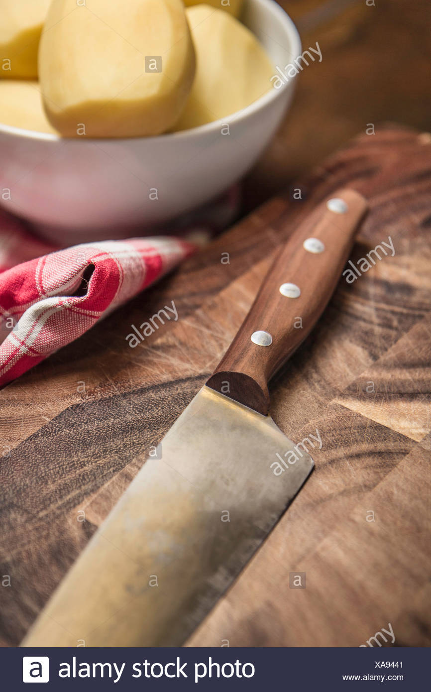Still life of peeled potatoes in bowl and kitchen knife - Stock Image
