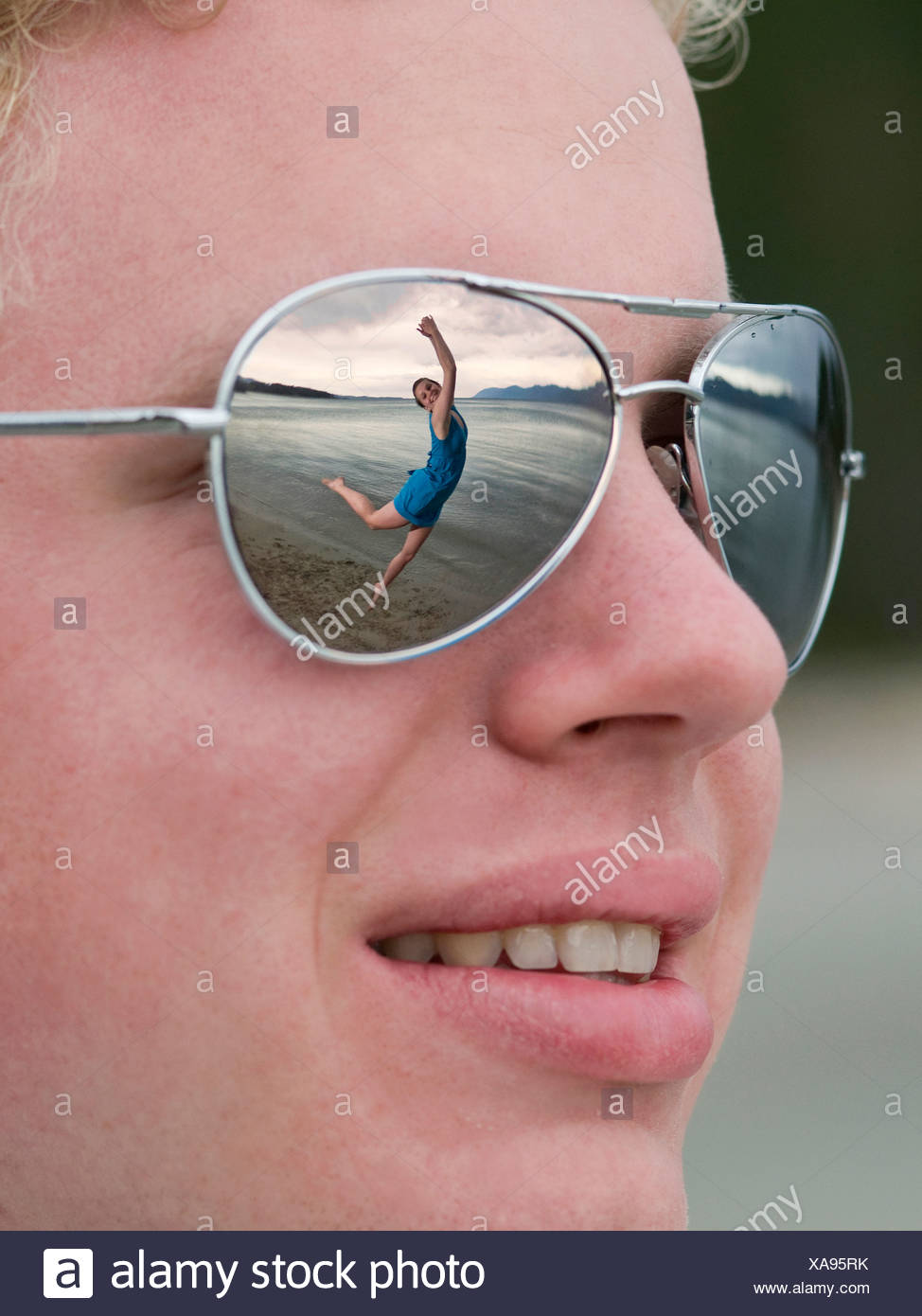 young man admires young lady she dances beach - Stock Image