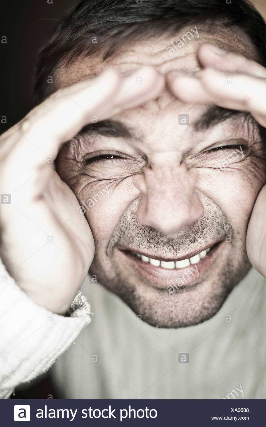 Close up of mature man making funny faces against black background, smiling - Stock Image