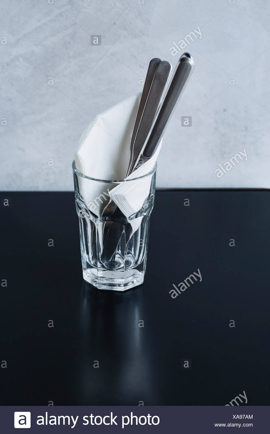 Flatware in glass on cafe table - Stock Image