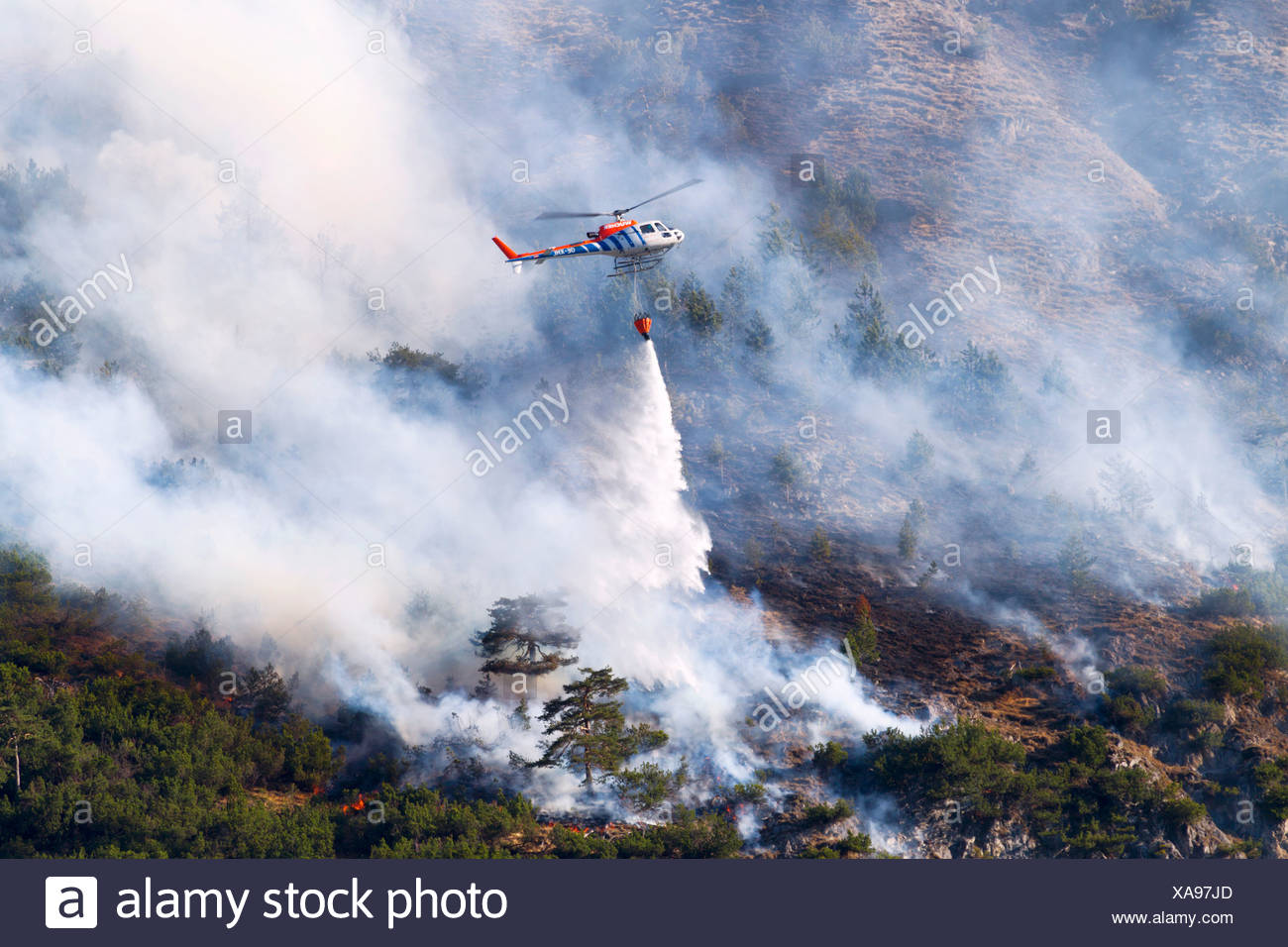 Helicopter dumping water during a forest fire, Tyrol, Austria - Stock Image