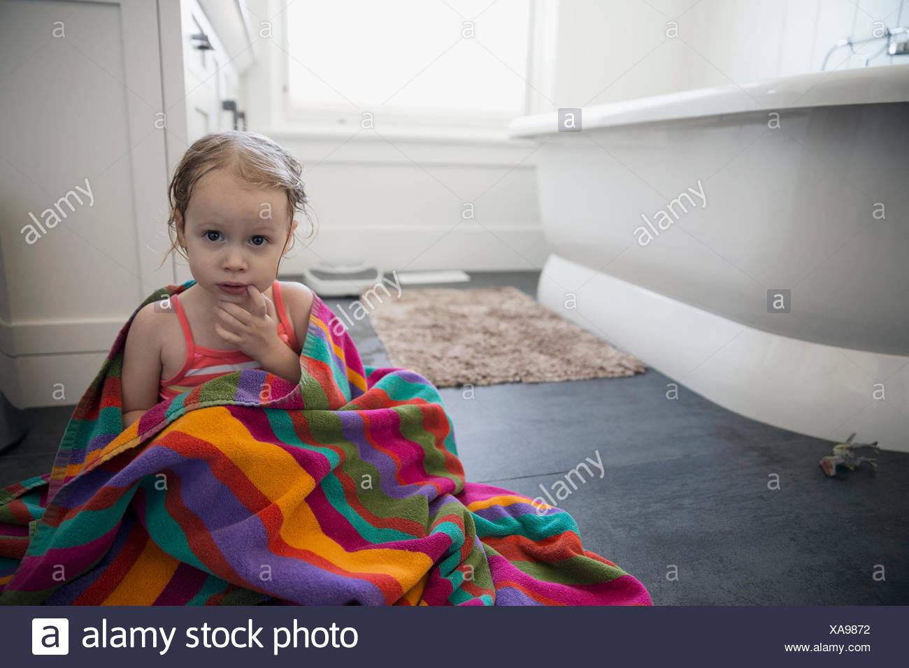 Portrait cute girl wrapped a towel bathroom floor - Stock Image