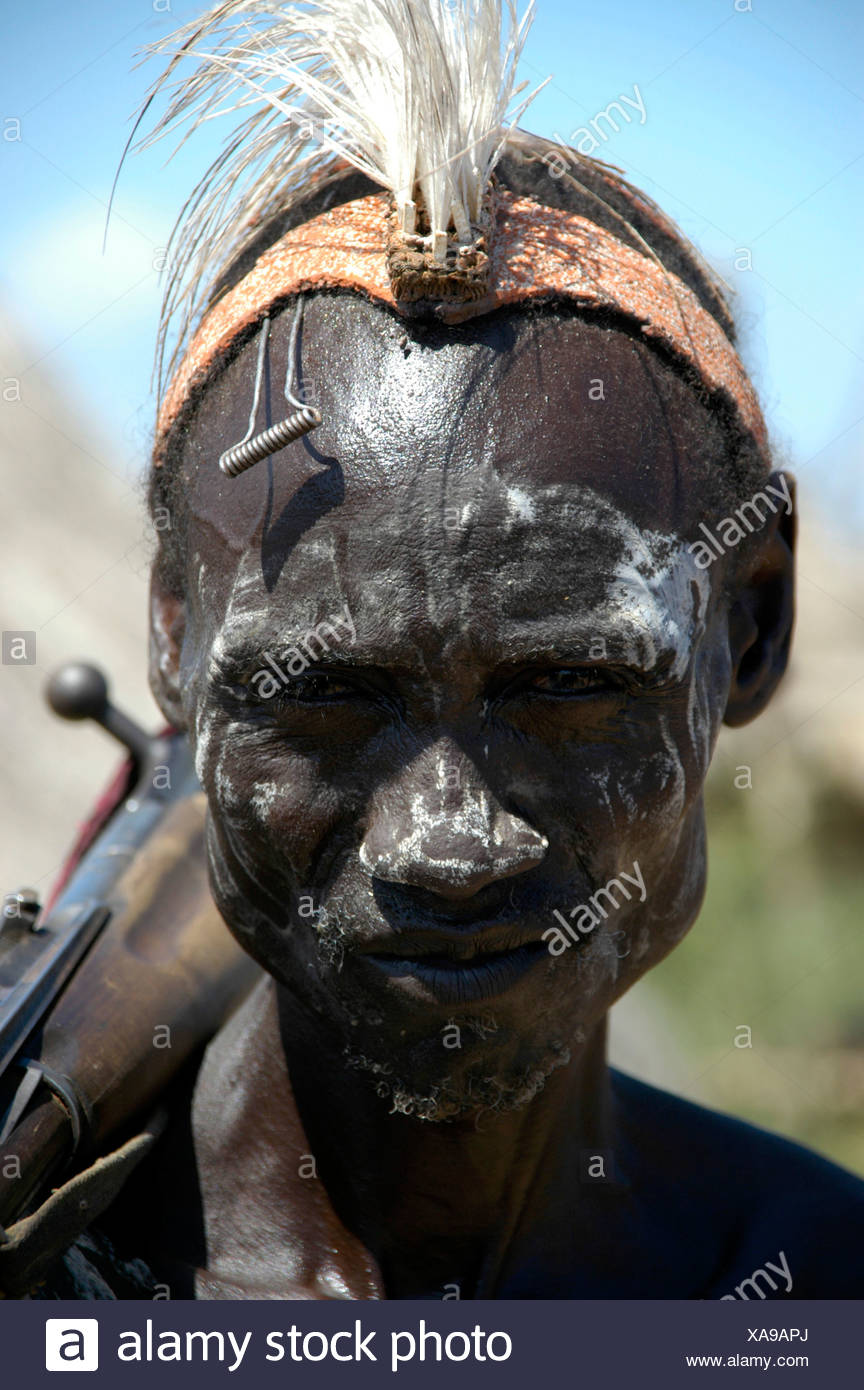 Karo tribesman wearing feathers in a headband and white paint on his face and shouldering a rifle, portrait, Kolcho, South Omo  - Stock Image