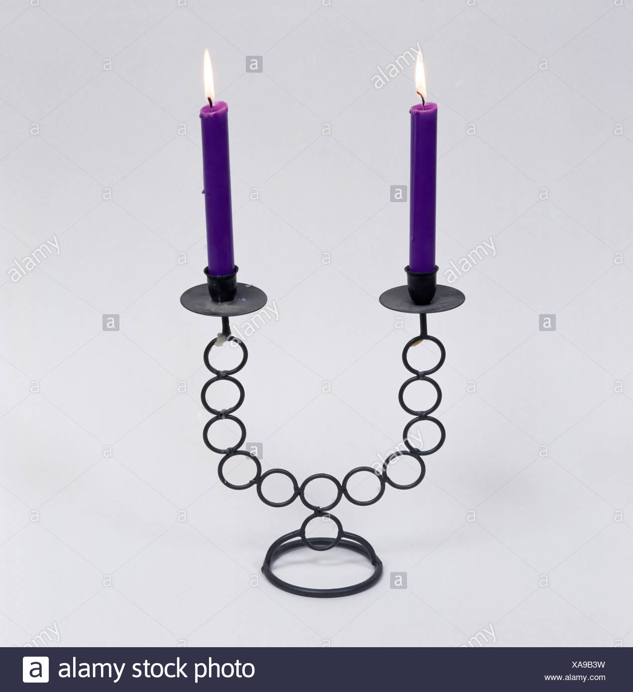 Close-up of purple candles in a metal candlestick - Stock Image