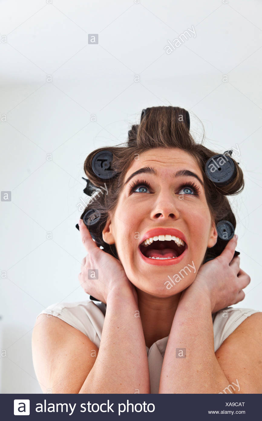 Young woman wearing hair rollers looking up - Stock Image