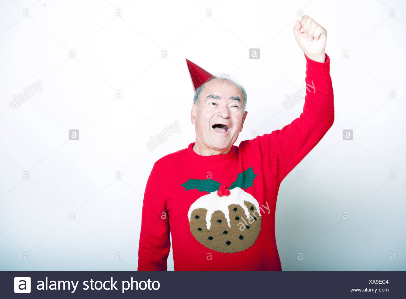Senior adult man wearing Christmas jumper raising his arm the air - Stock Image