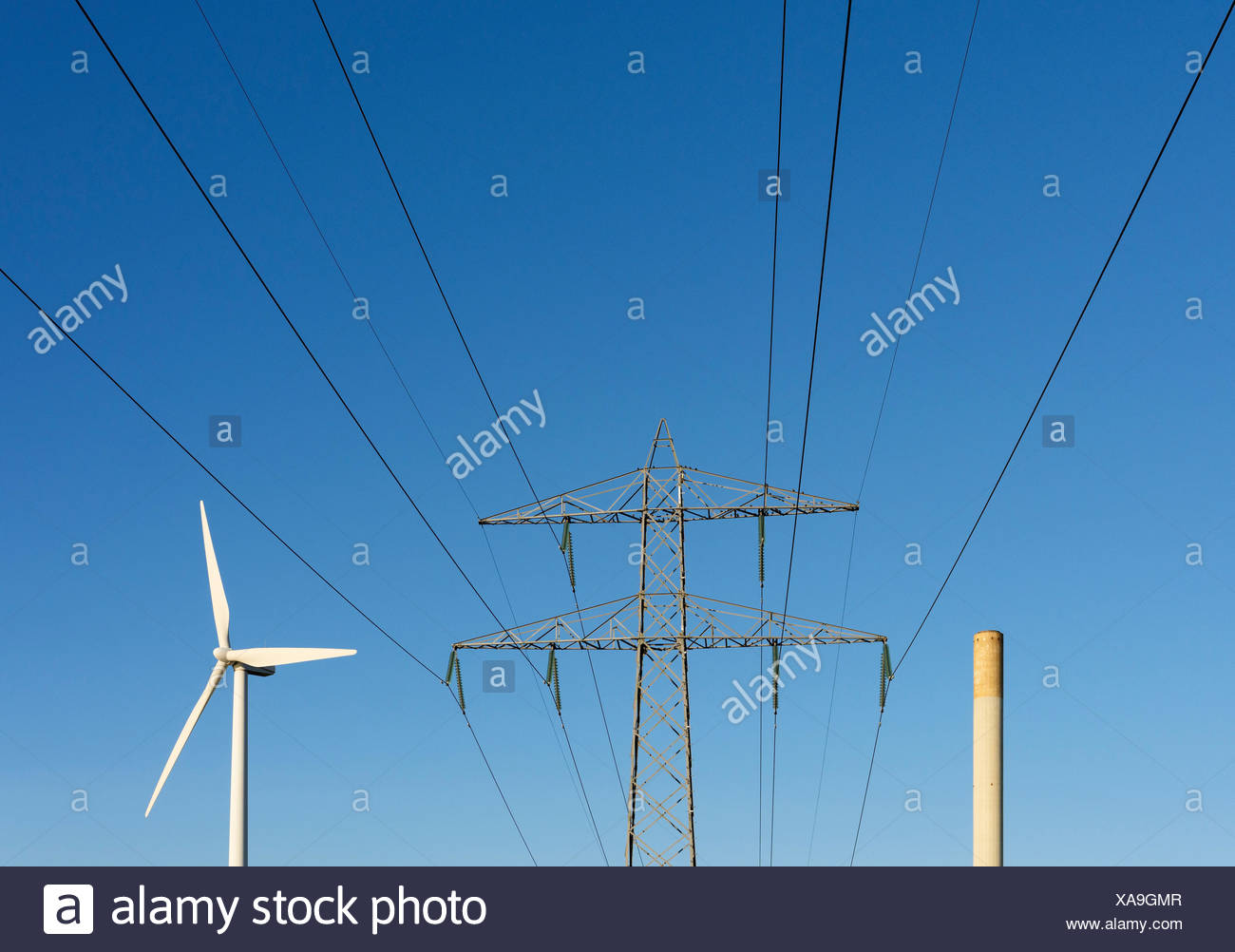 Chimney belonging to a coal-fired power station, and a modern wind turbine - Stock Photo