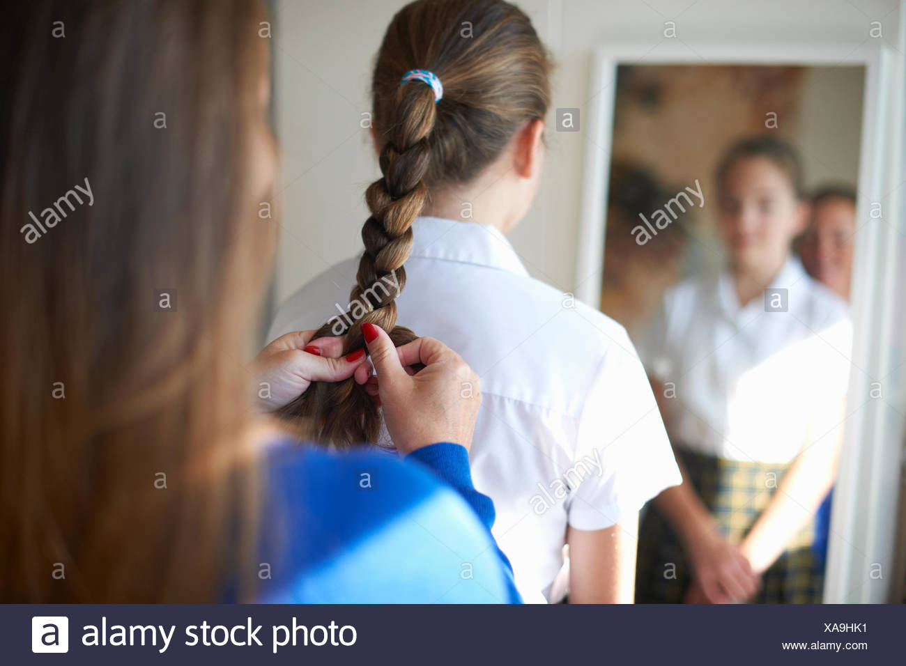 Over shoulder view of mother plaiting teenage schoolgirl daughter's hair - Stock Image