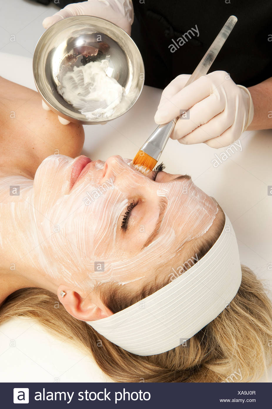 Woman getting a facial treatment at a spa - Stock Image