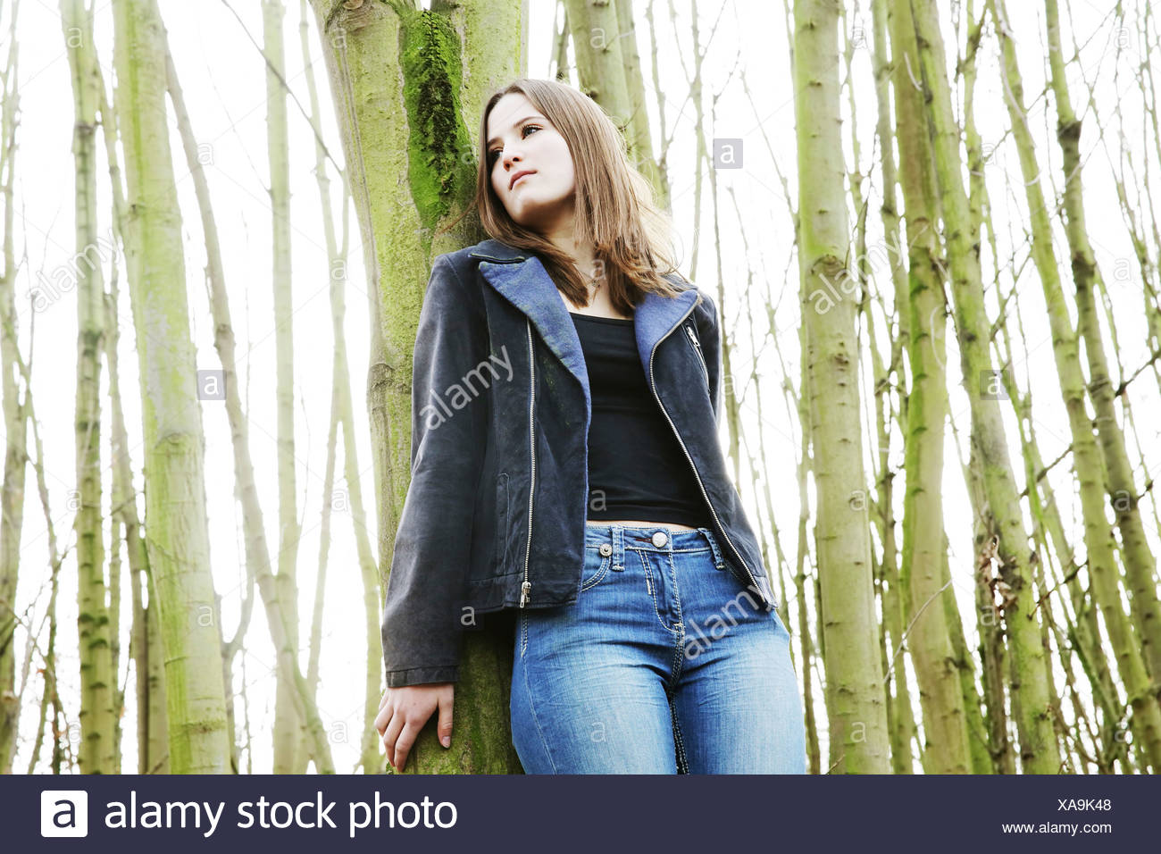 Portrait of teenage girl leaning against tree trunk - Stock Image