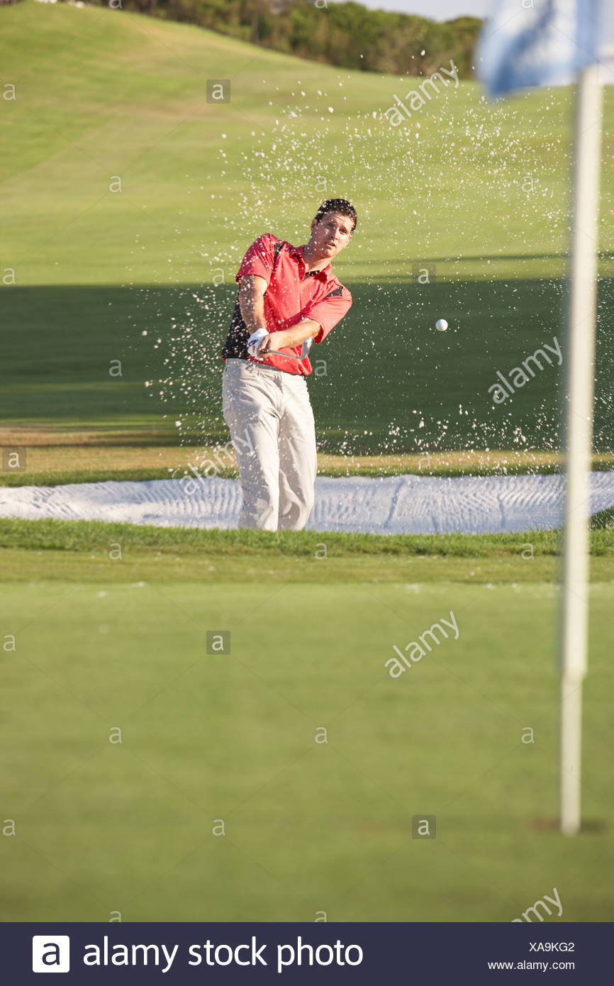Male Golfer Playing Bunker Shot On Golf Course - Stock Image
