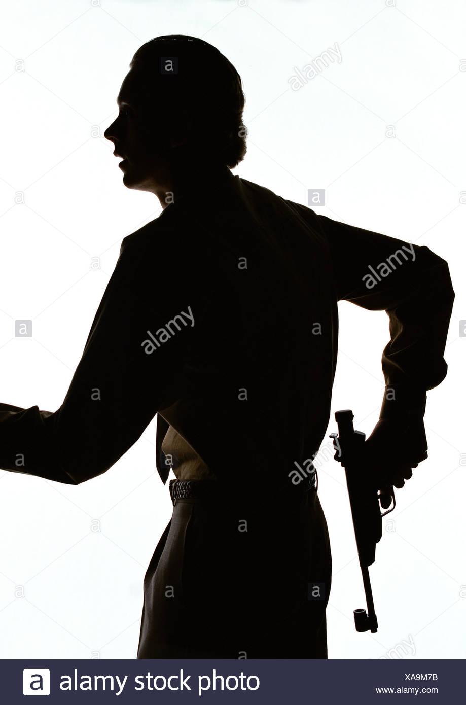 Man holding gun, silhouette. - Stock Image