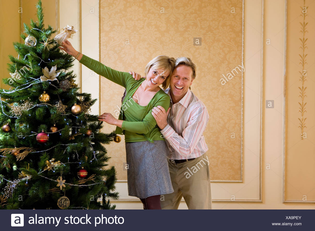 Angel Of Christmas.Couple Indoors Putting Angel On Top Of Christmas Tree