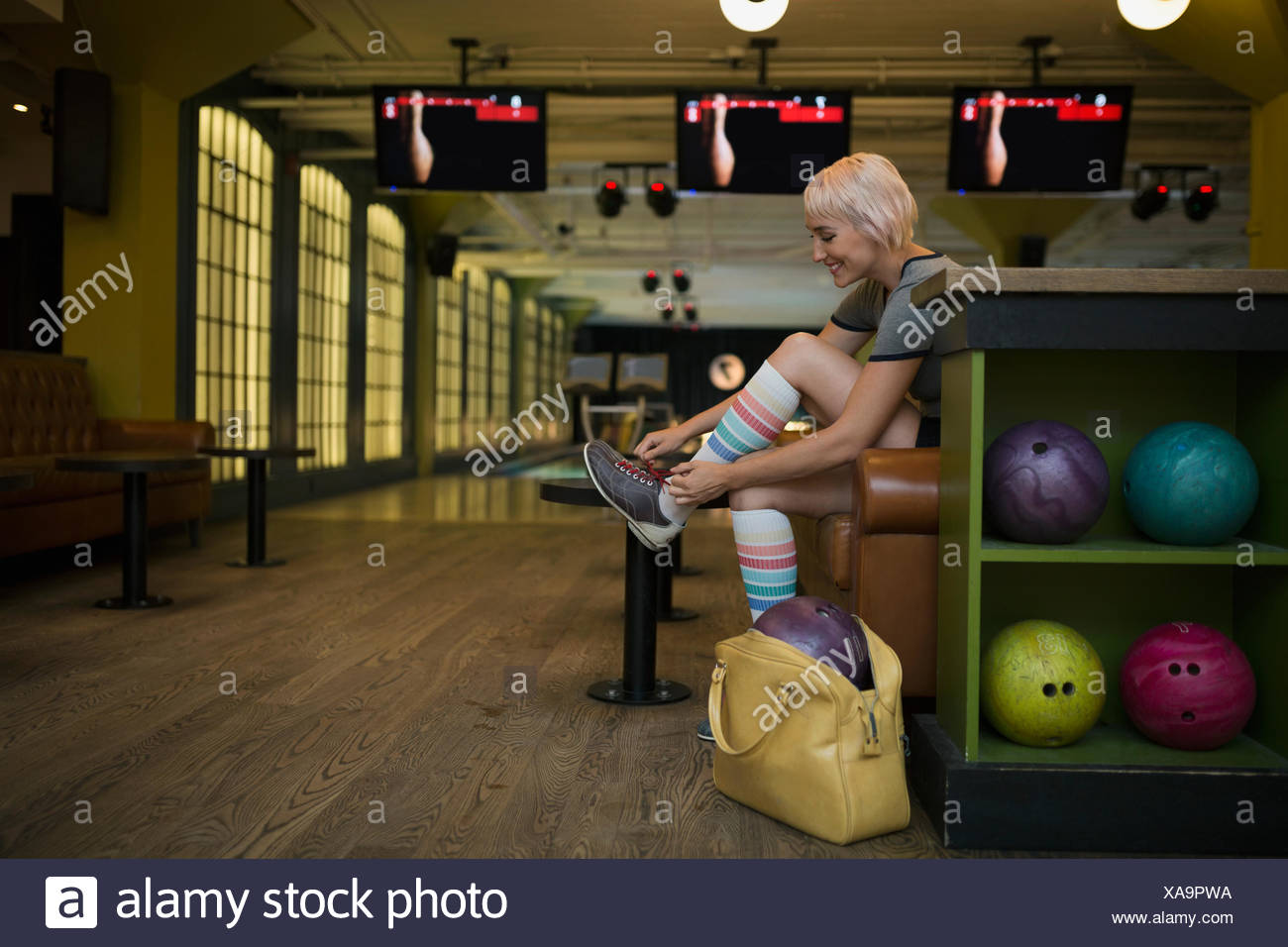 Young woman putting on bowling shoes bowling alley Stock Photo