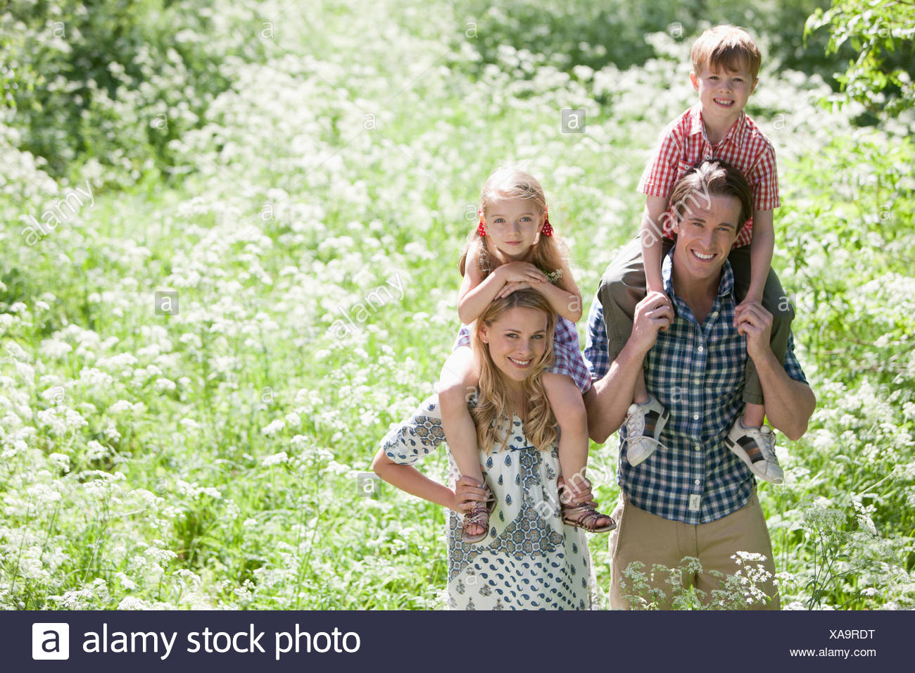 Parents holding children on shoulders in park Stock Photo