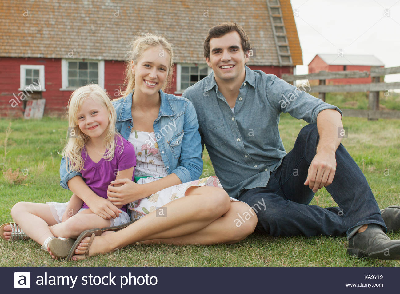 Portrait of young family on rural property. - Stock Image