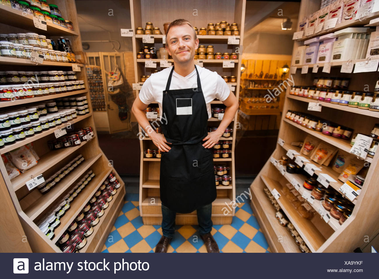 Full length portrait of mid adult salesman standing hands on hips in grocery store - Stock Image