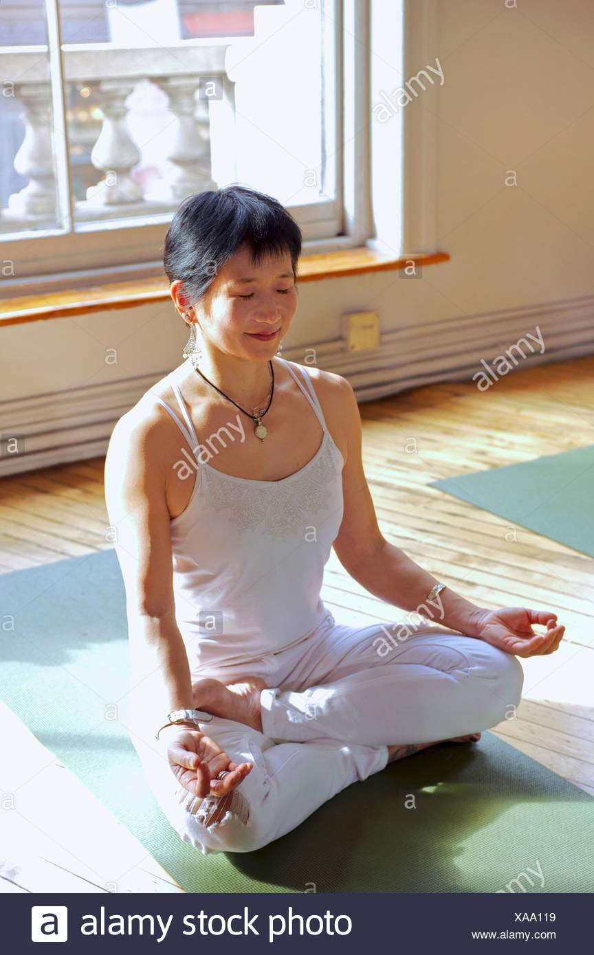 Mature woman in lotus pose - Stock Image