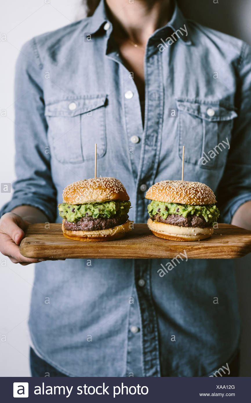A woman is photographed from the front view while holding two guacamole burgers in her hand on a wood cutting board. - Stock Image