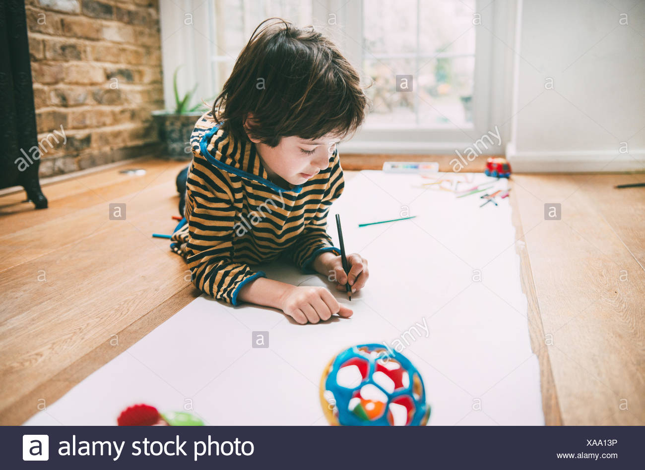 Boy lying on floor drawing on long paper - Stock Image
