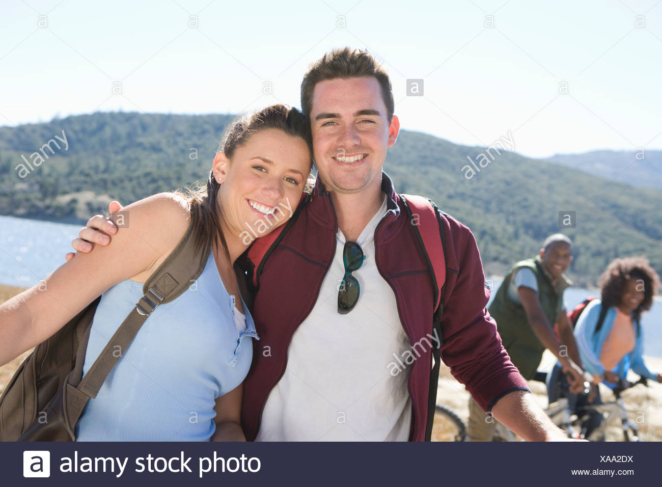 Young couple stand at lakeside, man with his arm around the woman - Stock Image