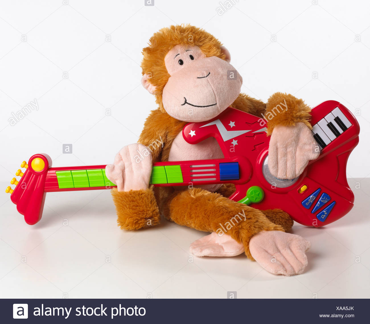 Toy monkey playing guitar, close-up - Stock Image