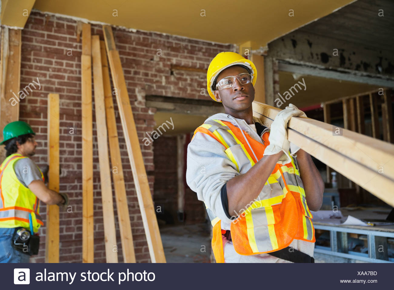 Tradesmen carrying lumber at construction site - Stock Image
