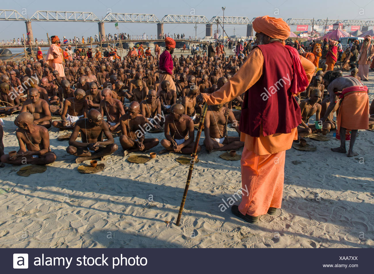 Taking their first meal in their new lives as part of the initiation of new sadhus at the Sangam, the confluence of the rivers - Stock Image