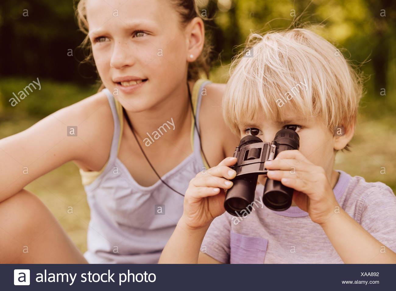 Boy looking through binoculars with his sister - Stock Image