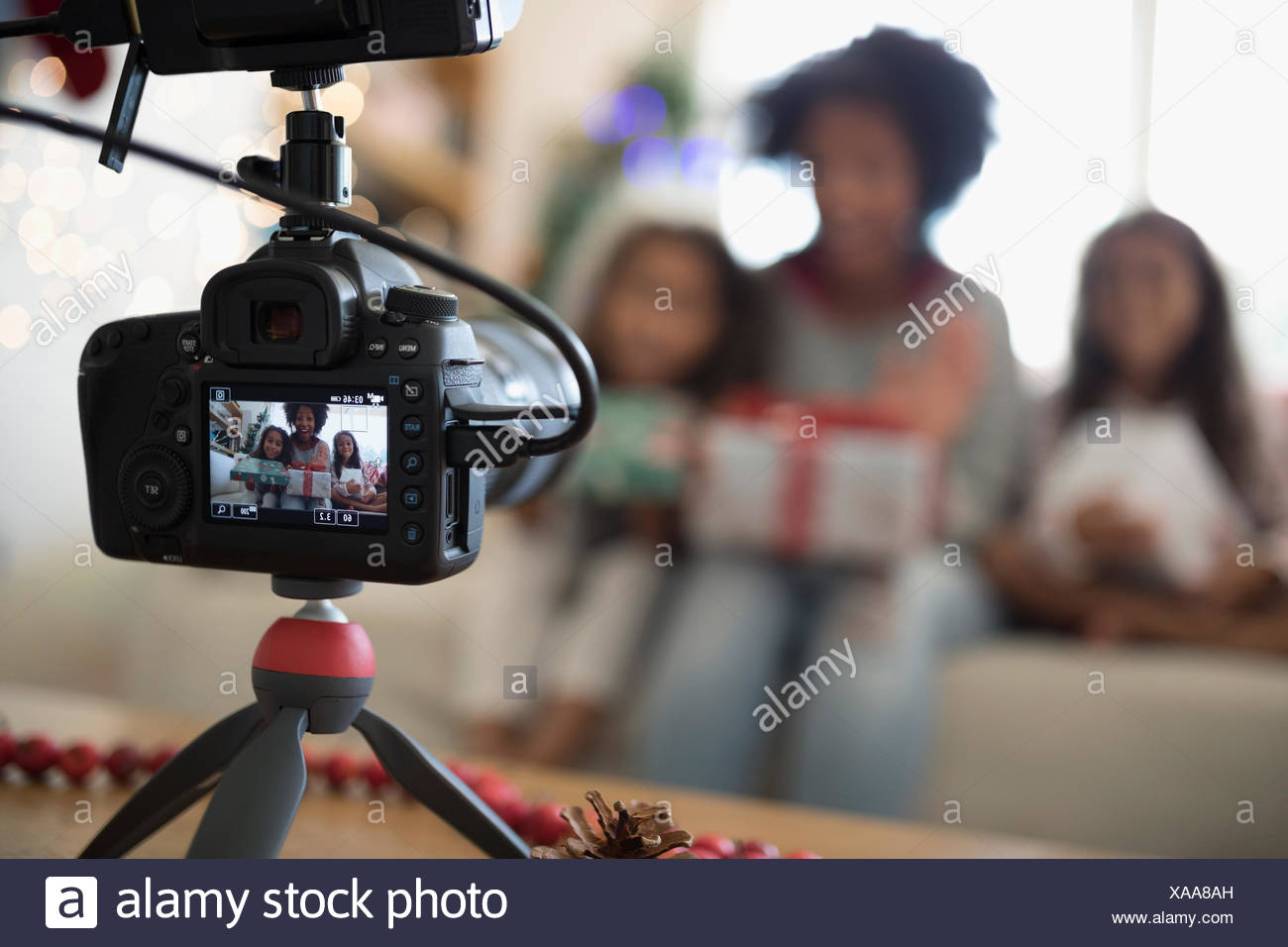 View through camera viewfinder of mother and daughters opening Christmas gifts - Stock Image