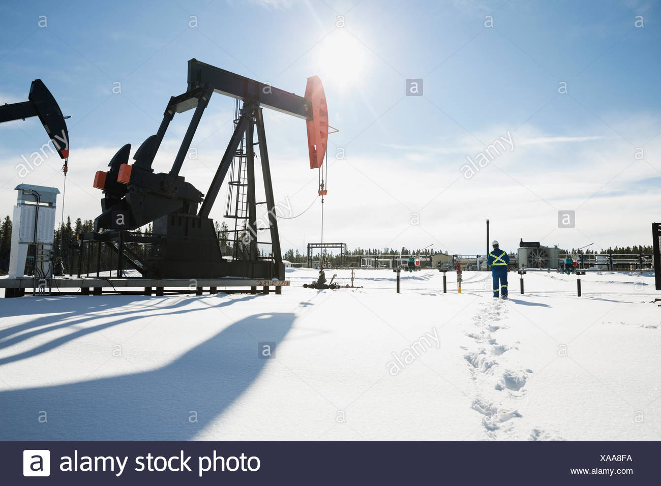 Worker walking toward drilling rigs in snow - Stock Image