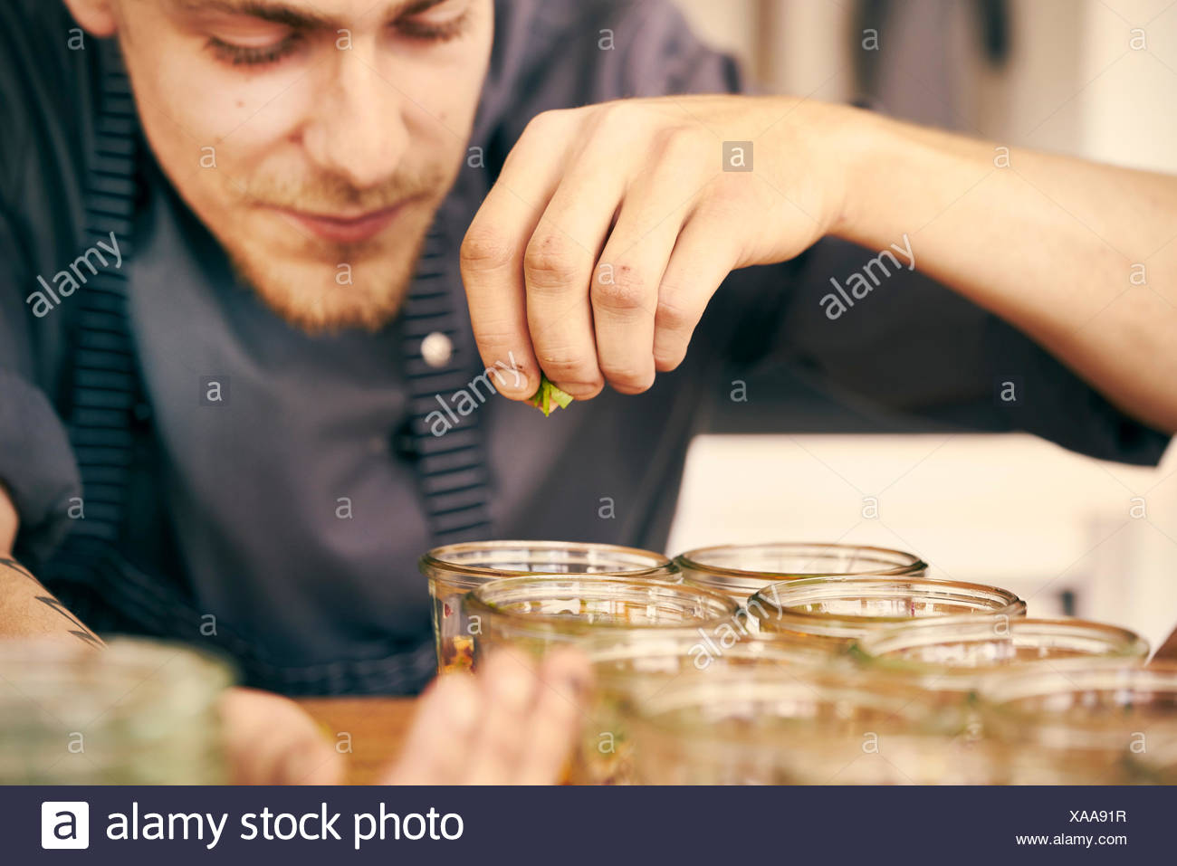 Chef seasoning food in plastic containers - Stock Image
