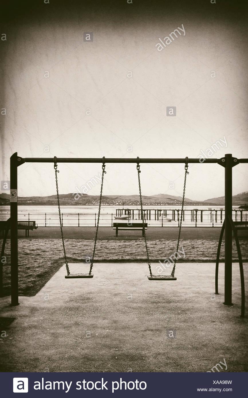 Deserted playground morning swings coast toned - Stock Image