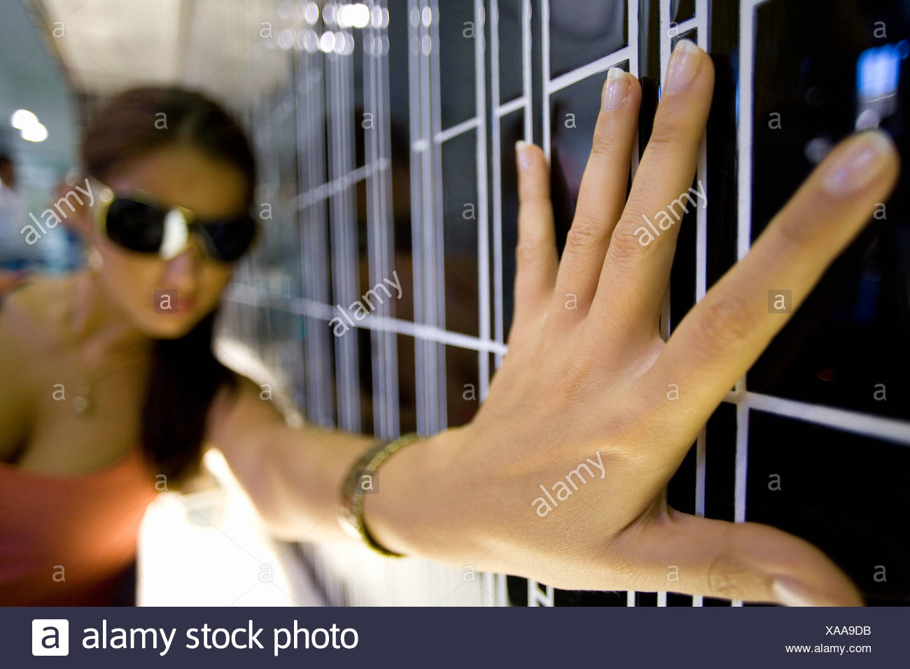 Young woman with hand on wall, wearing sunglasses - Stock Image