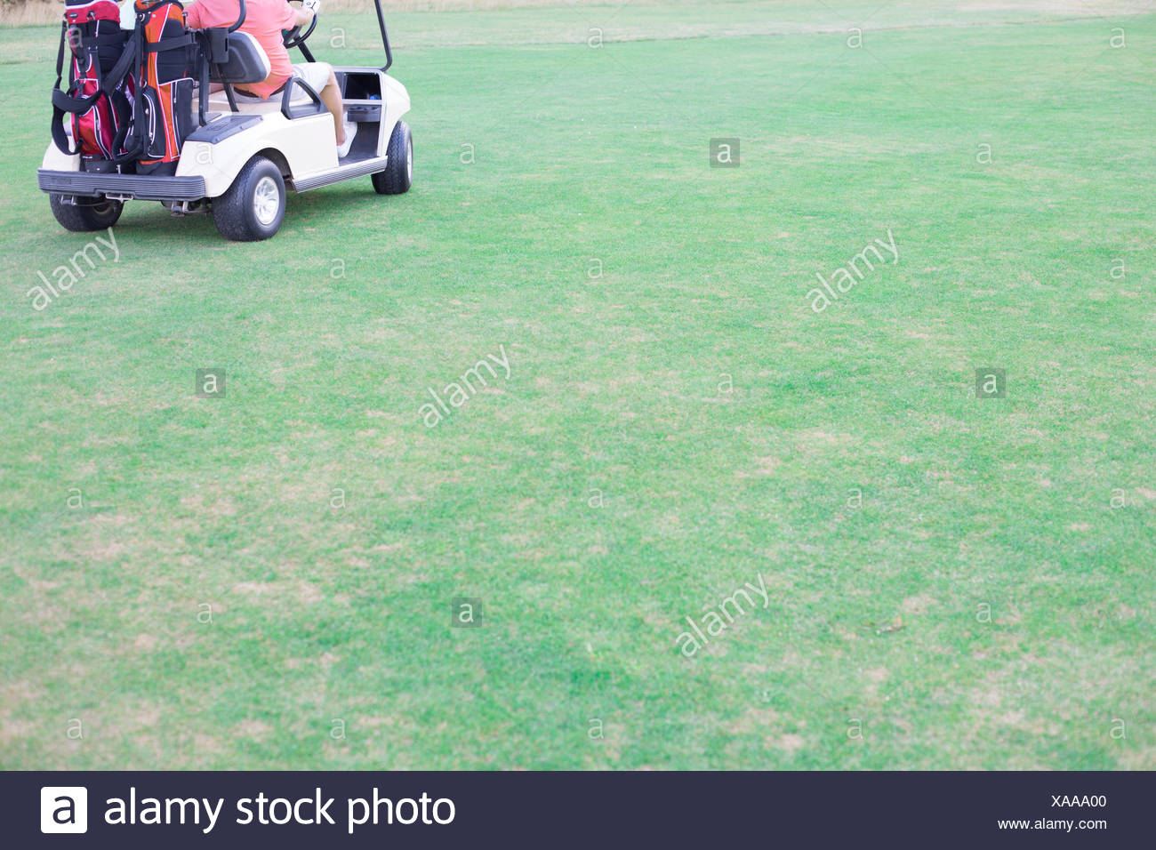 Low section of middle-aged man driving golf cart Stock Photo