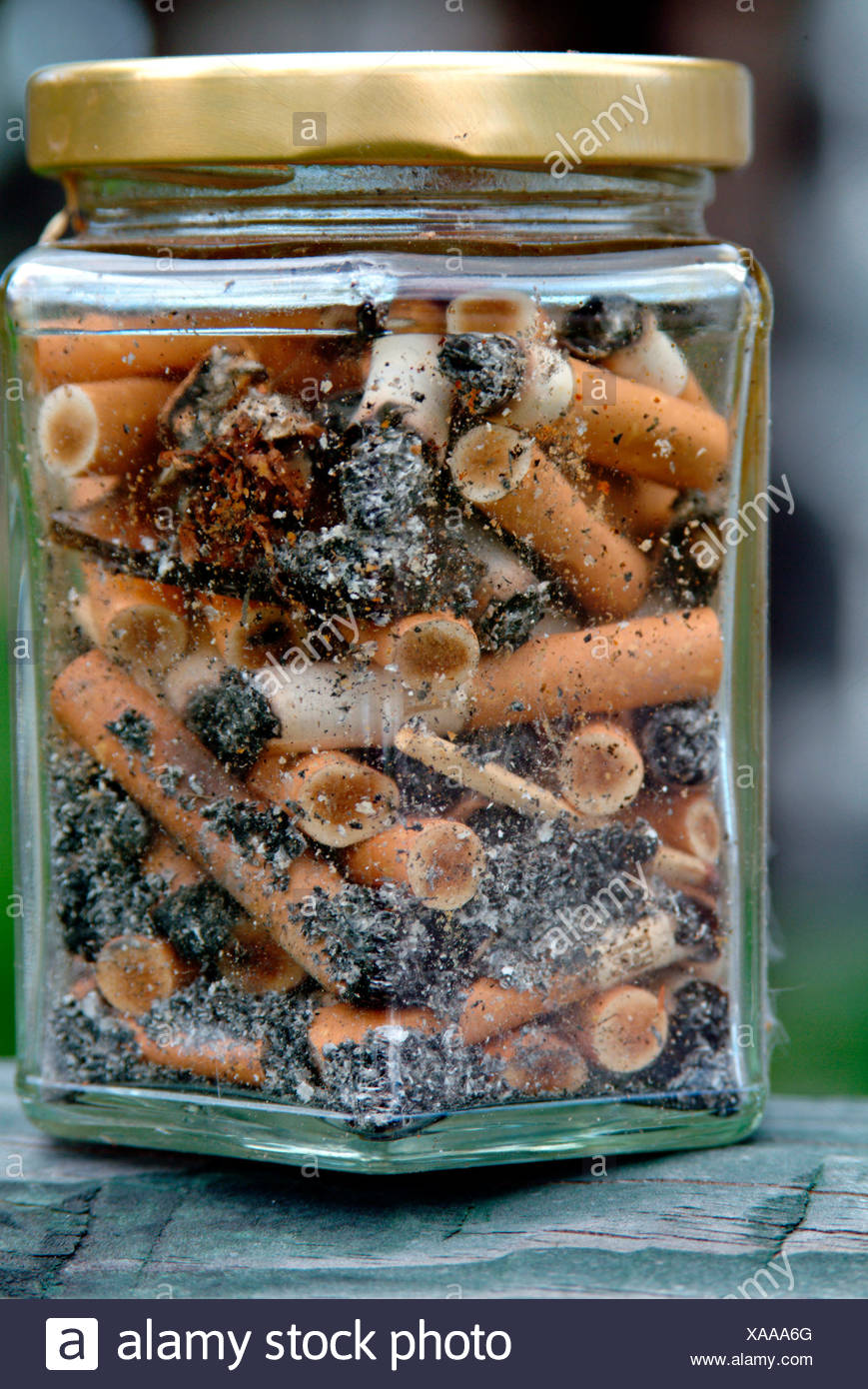 Close-up of jar of cigarette butts - Stock Image