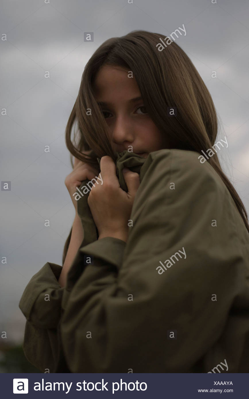 Female shielding face from cold behind coat lapel, portrait - Stock Image