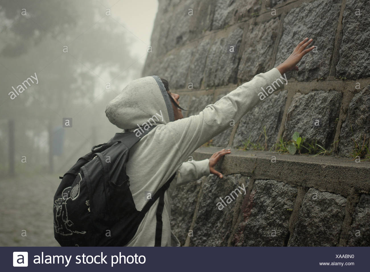 Teenager Touching Stone Wall - Stock Image