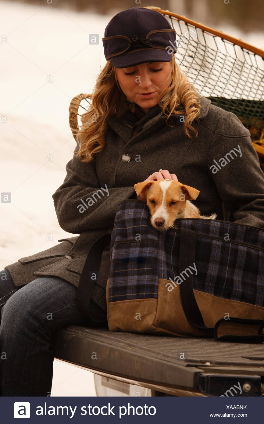 Woman Dressed In Winter Clothing Holding A Jack Russell
