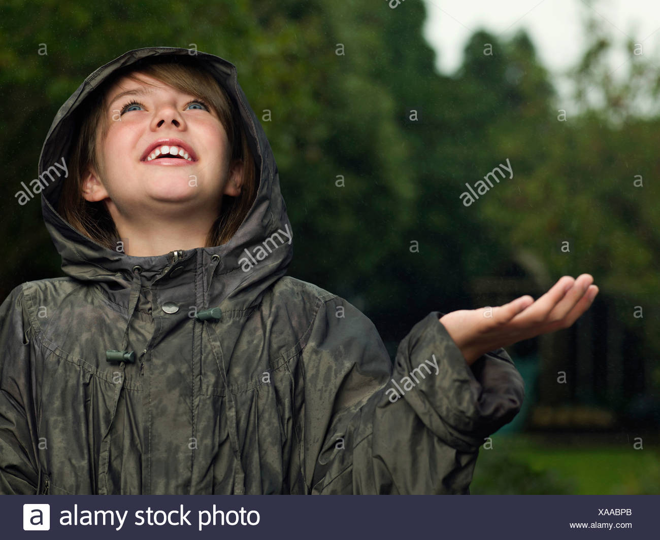 Girl holds hand out to catch rain - Stock Image