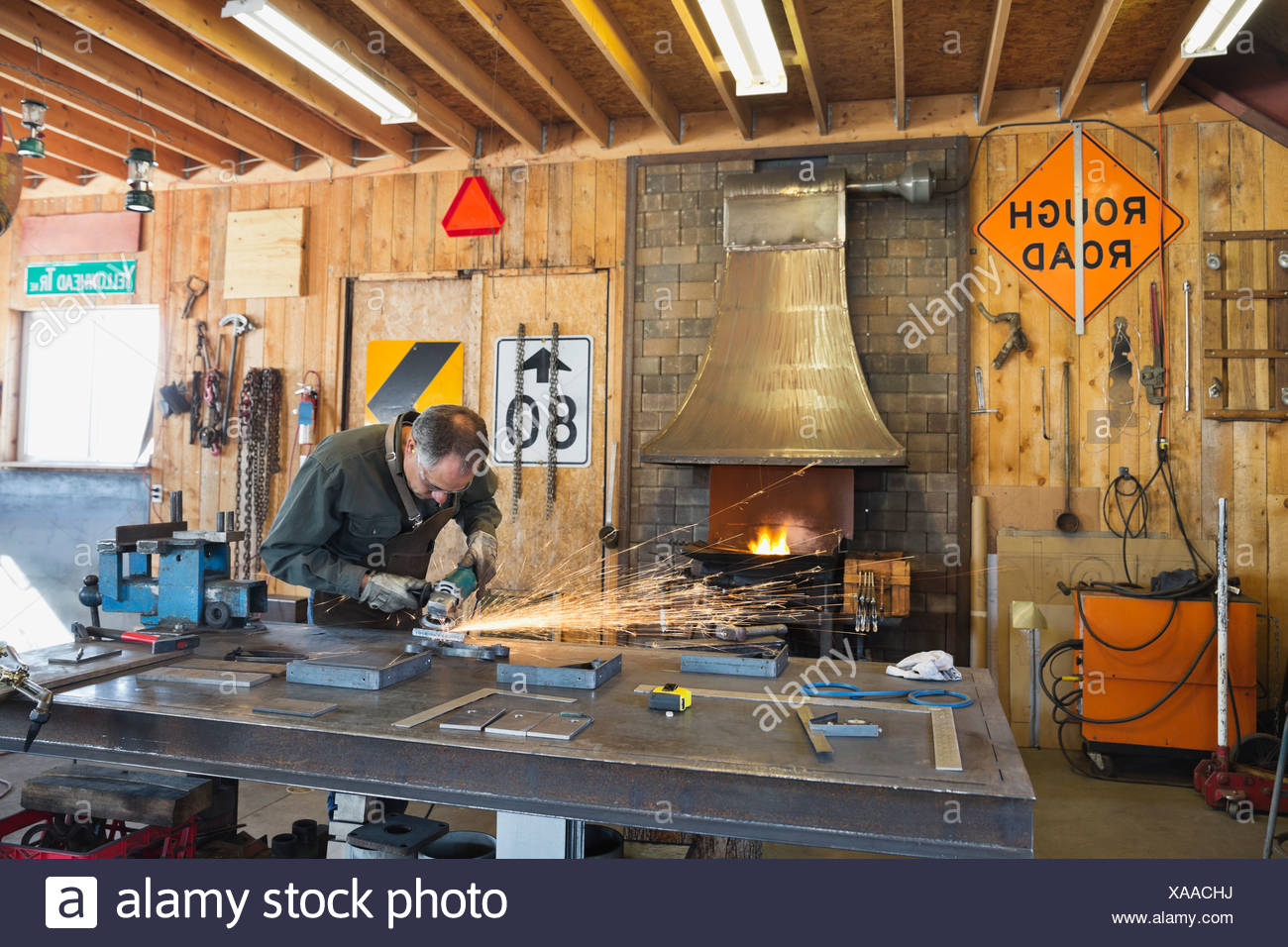 Worker grinding metal at workbench - Stock Image