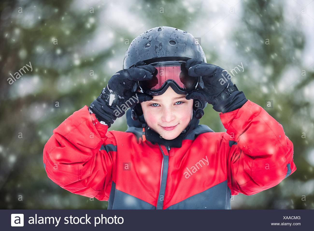 Boy wearing helmet and skiing goggles looking at camera smiling, snowing - Stock Image