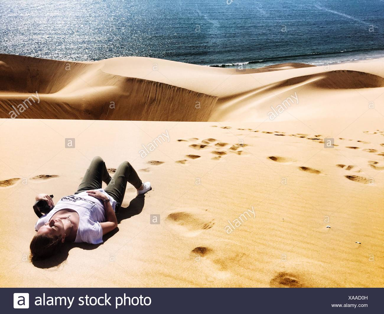 High Angle View Of Woman Relaxing On Desert By Sea - Stock Image