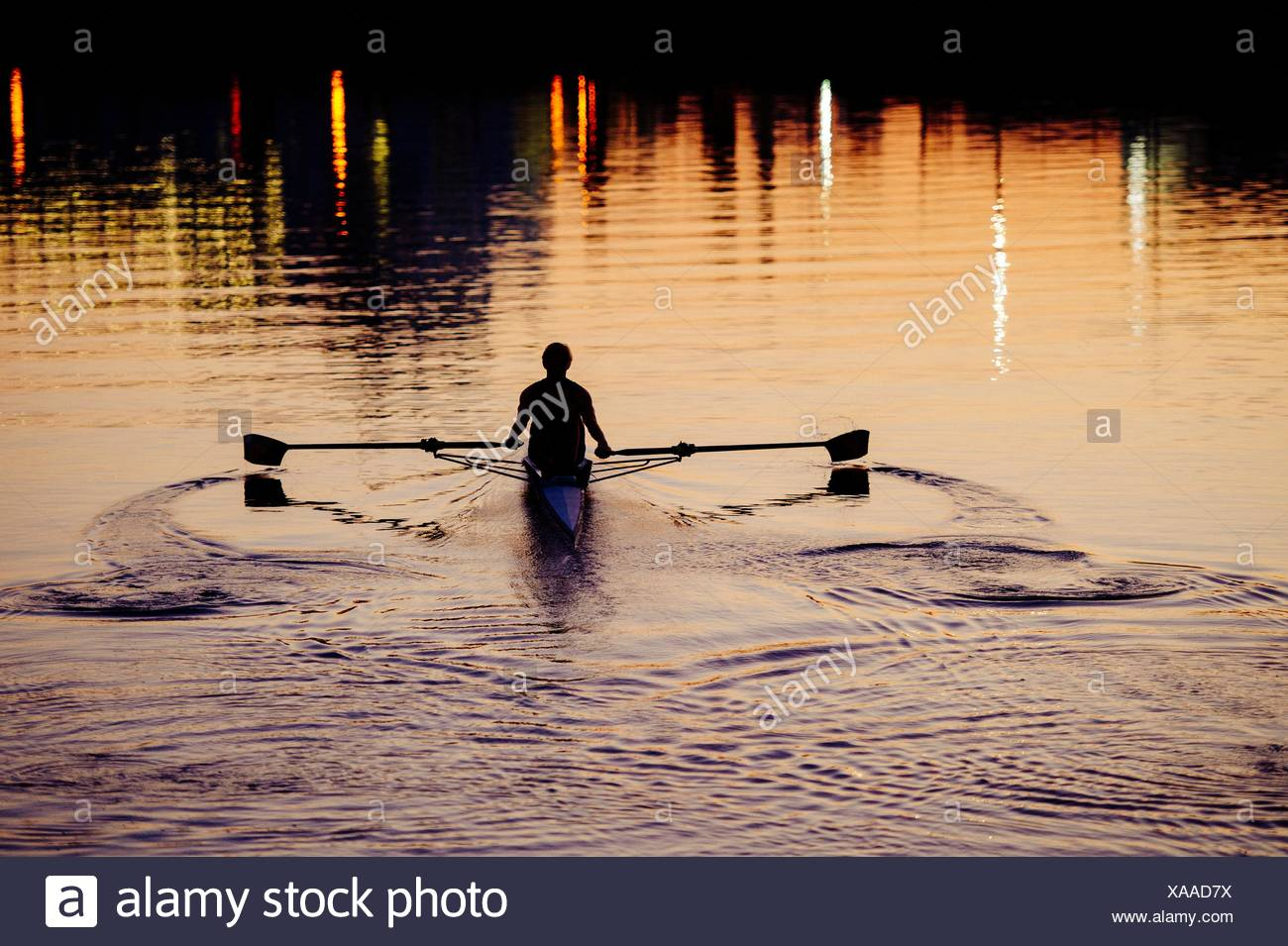 Young man rowing on river at sunset Stock Photo