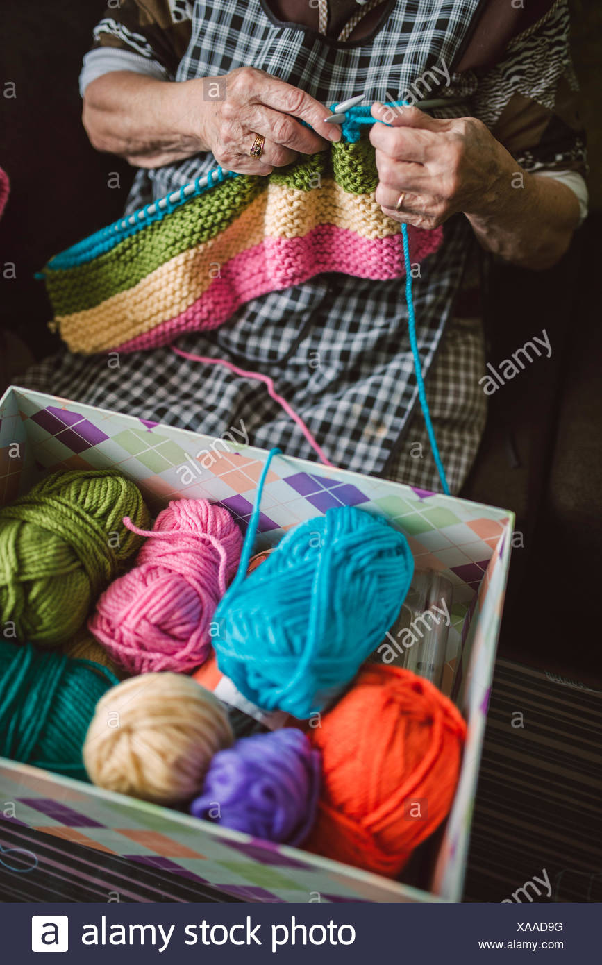 Box of different balls of wool and knitting senior woman Stock Photo