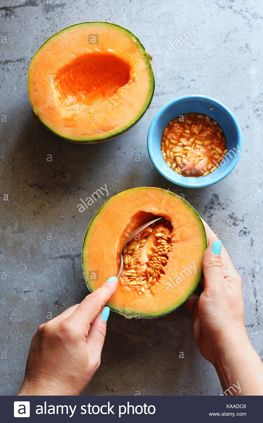Female hand scooping out the seeds from a cantaloupe.Top view - Stock Image
