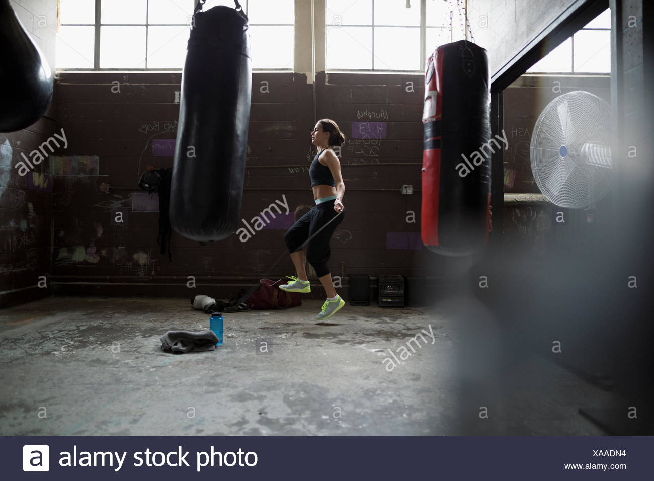 Female boxer jumping rope behind punching bags in gym - Stock Image