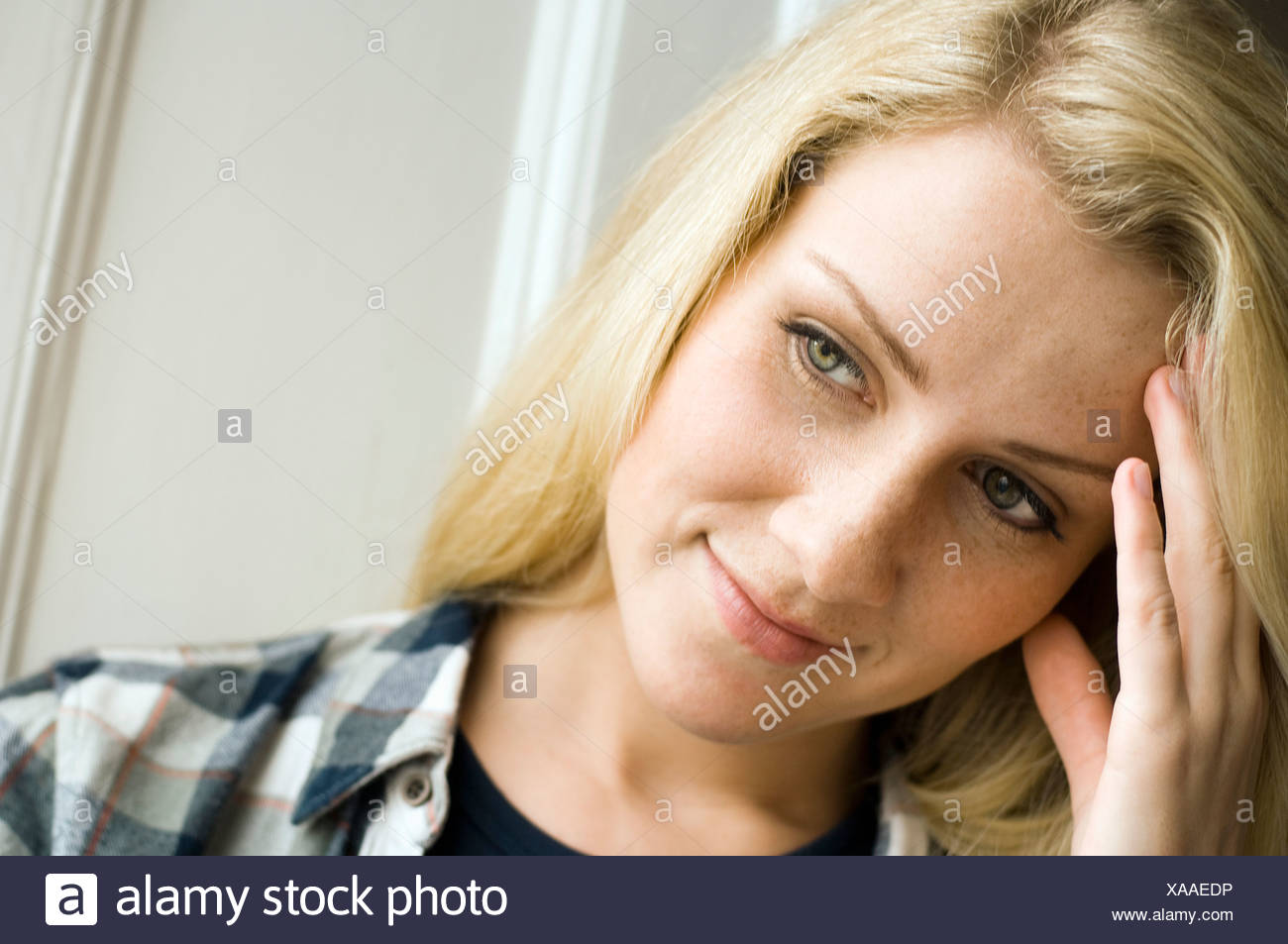 Close up of woman rubbing her forehead - Stock Image